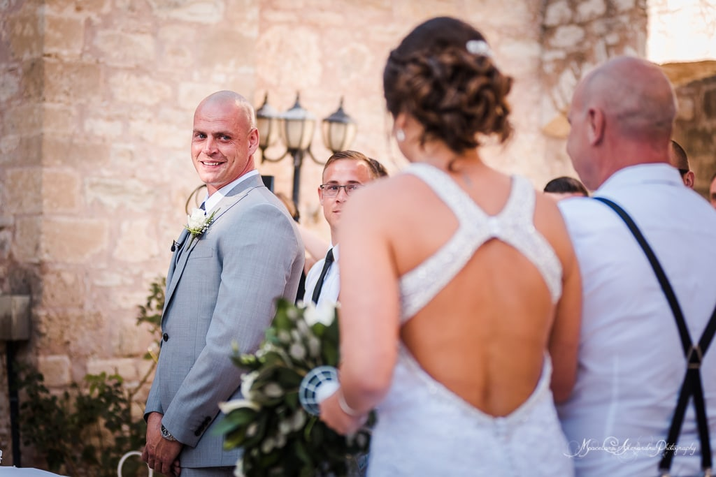 The groom looking at his bride for the first time, while she walks down the aisle for their wedding at Minthis Hills