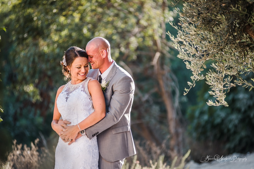 Steve holding Claire from the back in front of the monastery at Minthis Hills under an olive tree
