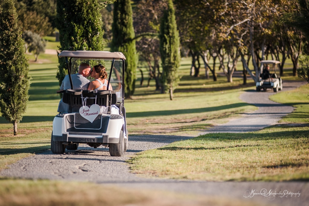 The newly weds having a ride on the golf buggy on Minthis Hills grounds