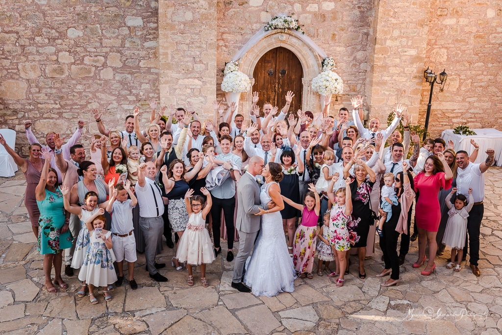 A beautiful group photo with all the guests cheering for the bride and groom, at the monastery