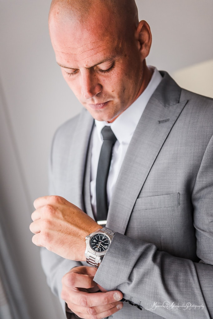 The portrait of the groom wearing his beautiful watch, so he will not be late at the wedding at Minthis Hills.