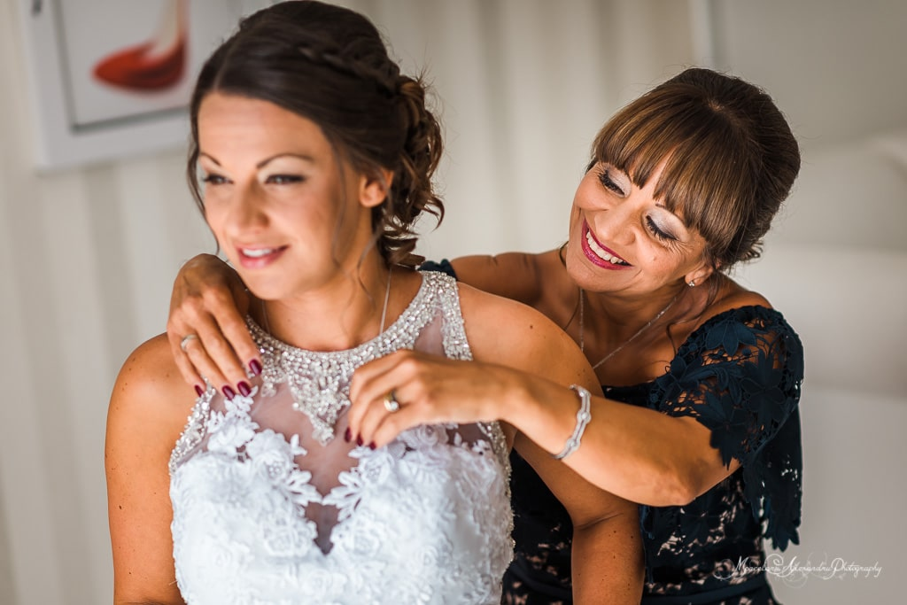 The moment when the mother of the bride help her to get ready. Wedding photography at Minthis Hills