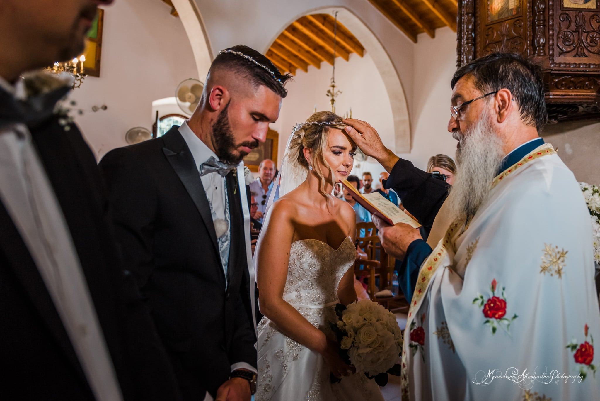 Wedding photography in Paphos - The priest is blessing the bride and groom