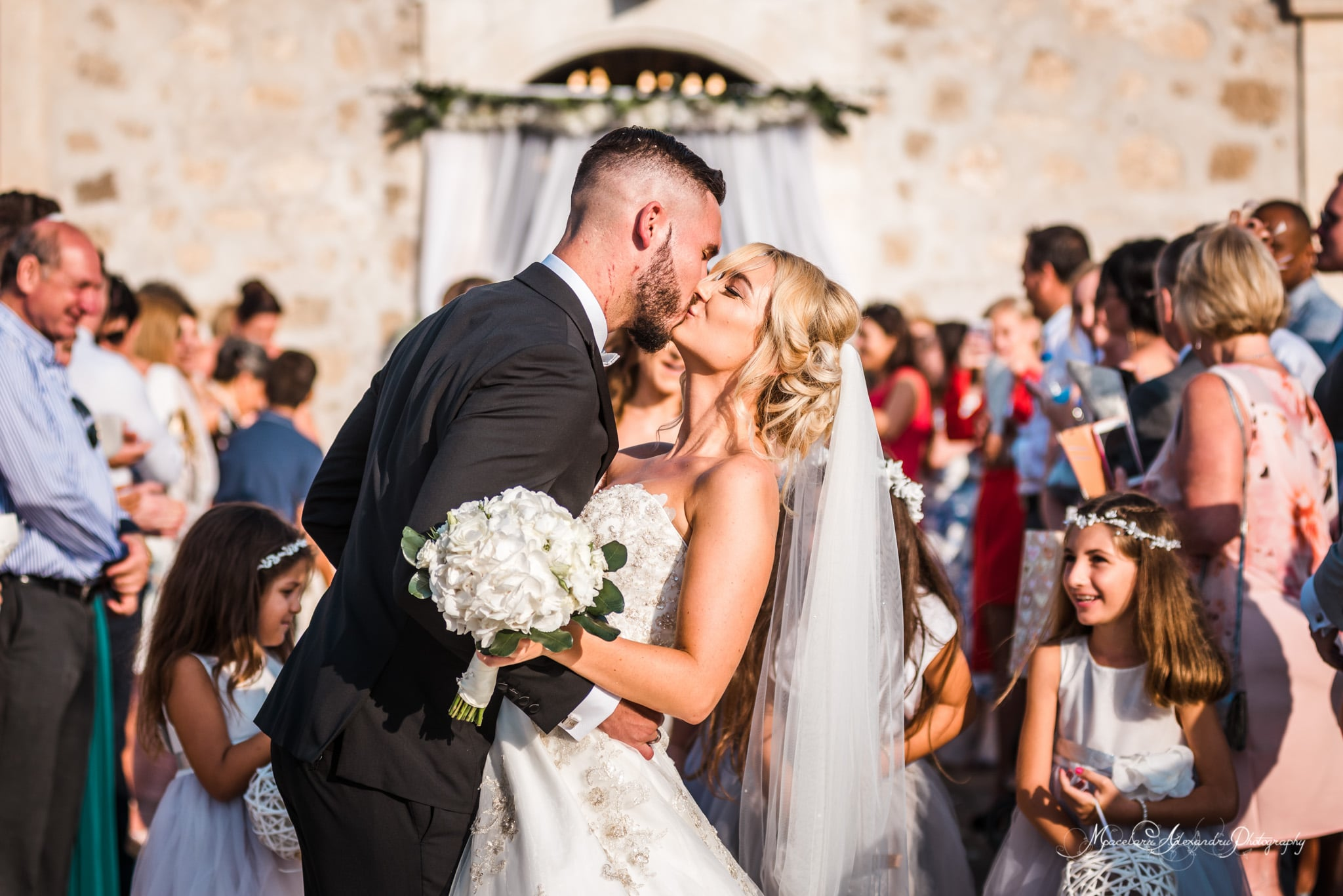 Wedding photography in Paphos - Bride and groom kiss in front of the church