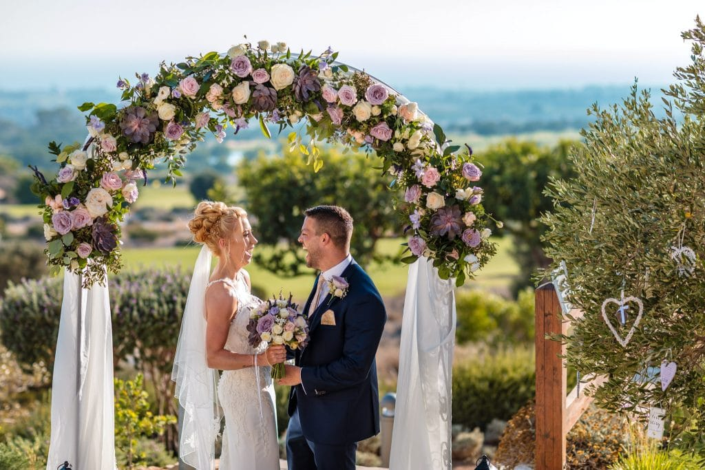 bride and groom under the ceremony arch